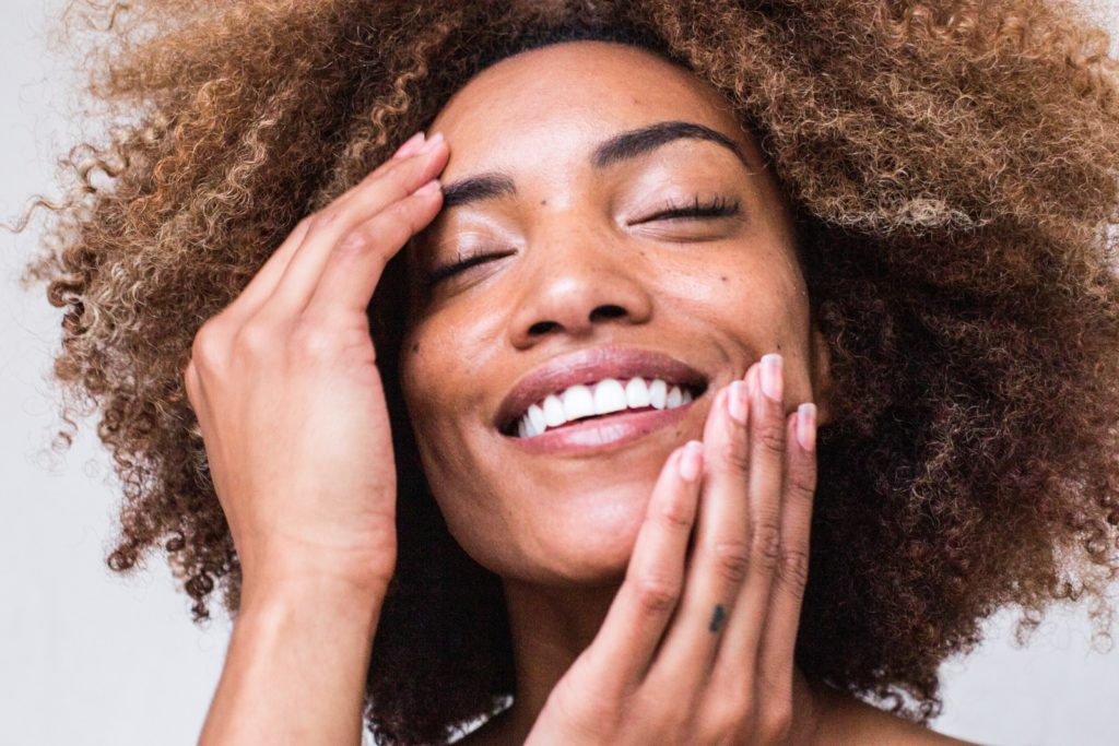 woman with glowing skin, touching her face happily